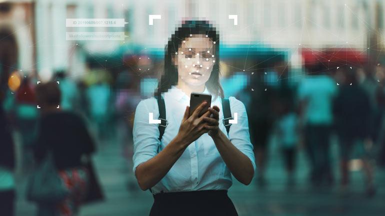 Vrouw met gezichtsherkenning en smartphone in haar hand.