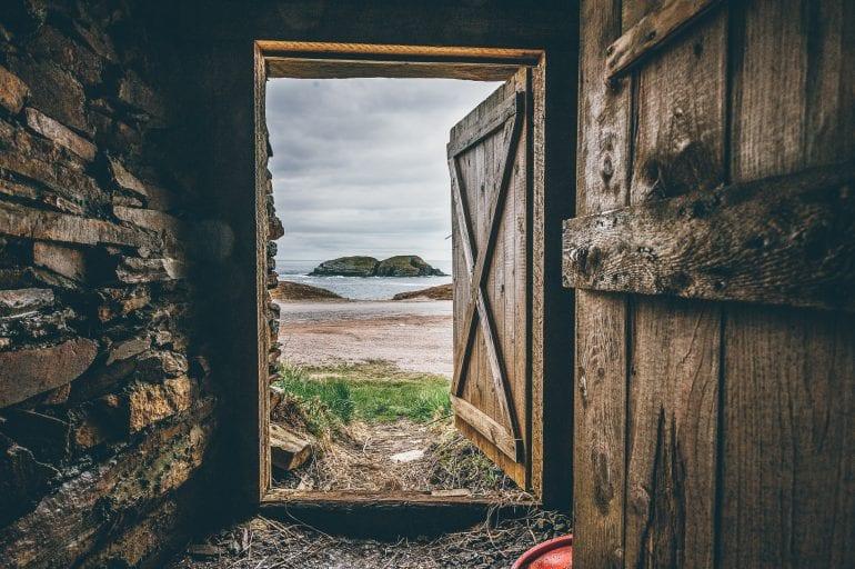 Foto van een open deur met daarachter strand en zee