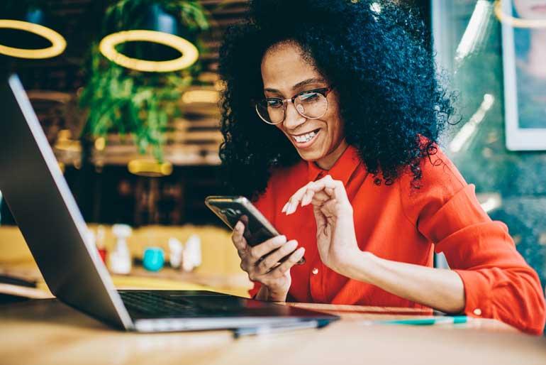 Vrouw bezig met smartphone, achter haar laptop.