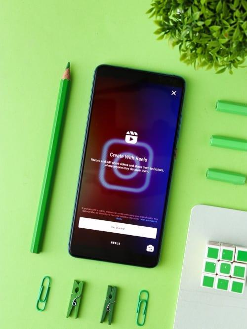 Smarphone met Instagram Reels op groene achtergrond