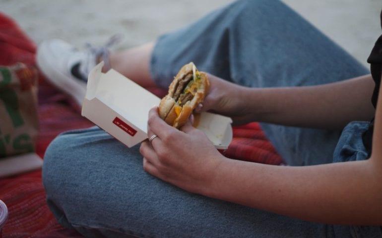 Persoon in spijkerbroek houdt burger McDonalds vast