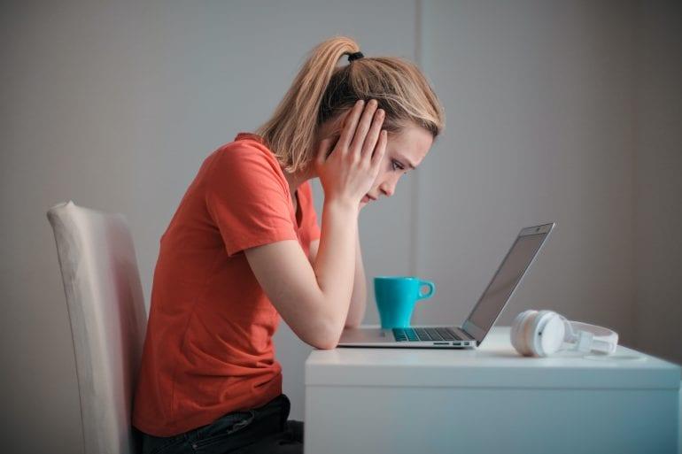 Vrouw kijkt verbaasd naar computerscherm.